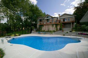 beautiful inground pool on beautifully landscaped yard with fence